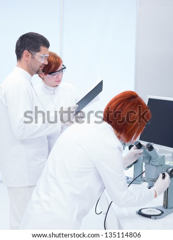 close-up of a man in a chemistry lab proposing and explaining hypotheses to the students and supervising lab experiments - stock photo