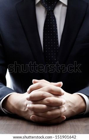 close up of a man in a suit with his hands clasped in front of h - stock photo