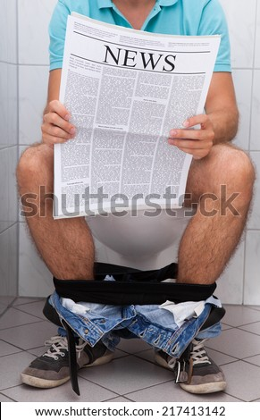 Close-up of a man in toilet reading newspaper indoors - stock photo