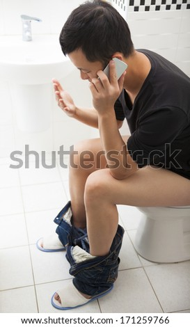 Close-up of a man in toilet talking with smart phone - stock photo