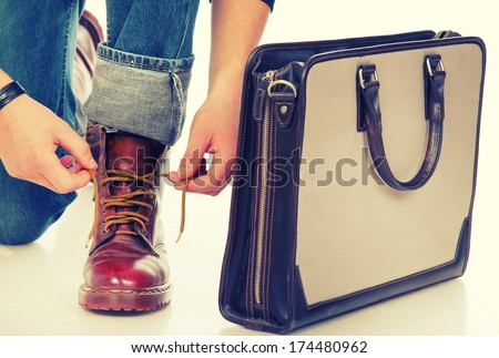 Close-up of a man lacing boots and a briefcase - stock photo