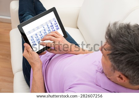 Close-up Of A Man Looking At Calendar In Digital Tablet - stock photo