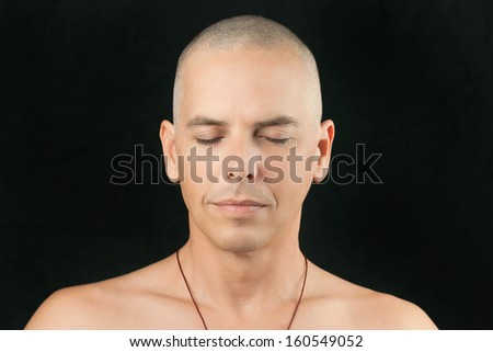Close-up of a man meditating, shaved head and shirtless. - stock photo
