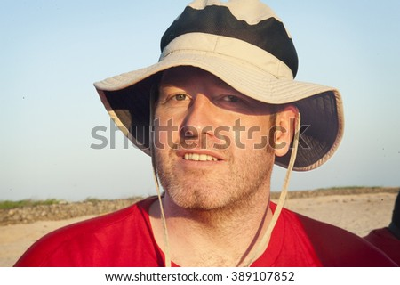 Close-up of a man on beach wearing hat - stock photo