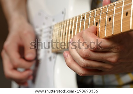 Close up of a man playing a guitar. Shallow depth of field.