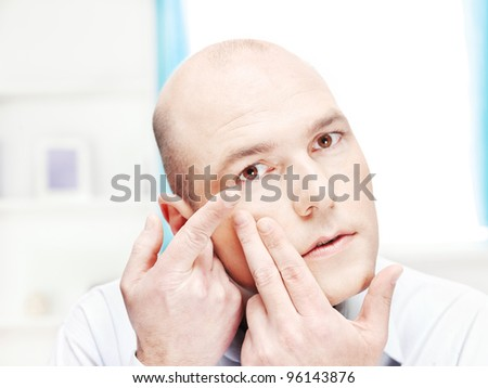 Close up of a man putting contact lens in his eye at home - stock photo