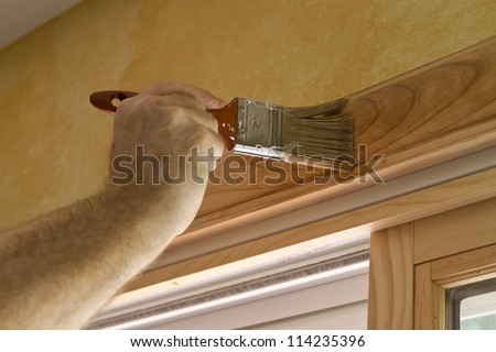 Close up of a man's arm and hand holding a paintbrush and staining a wooden door frame - stock photo