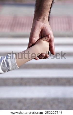 Close up of a man's hand and a child, to cross a zebra crossing.
