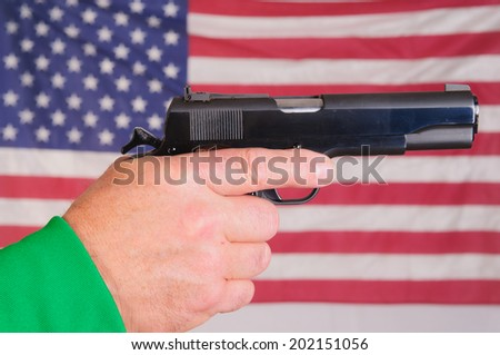 Close-up of a man's hand holding a cocked .45 ACP semi-automatic handgun infront of an American flag - stock photo