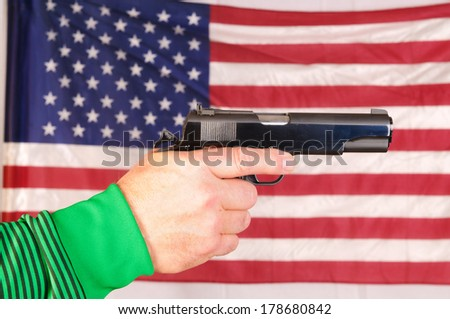close-up of a man's hand holding a semi-automatic pistol in front of an American flag - stock photo