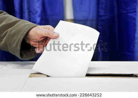 Close up of a man's hand putting a vote in the ballot box - stock photo