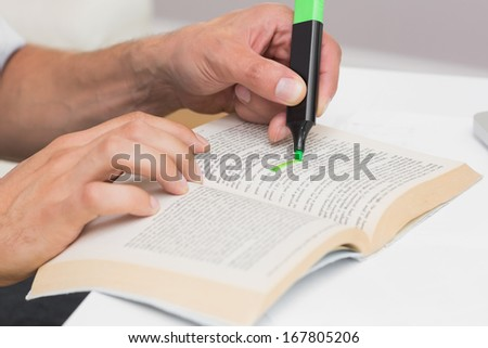 Close-up of a man's hands highlighting text in book on the table