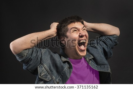 Close-up of a man screaming in agony.