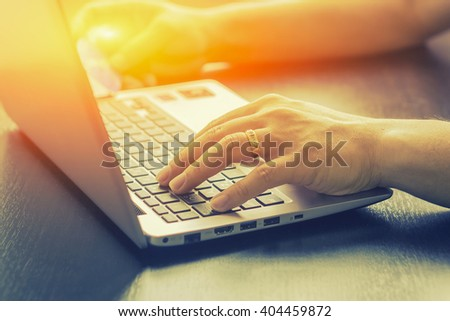Close Up Of A Man Shopping Online Using Laptop With Credit Card,male hands holding credit card typing numbers on computer keyboard at home at the wooden table,selective focus and vintage color. - stock photo