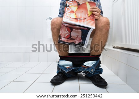 Close-up Of A Man Sitting On Commode Holding Sexy Magazine - stock photo