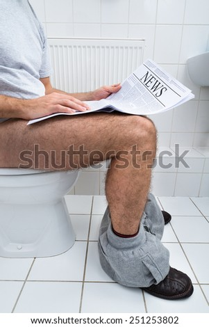 Close-up Of A Man Sitting On Commode Reading Newspaper - stock photo