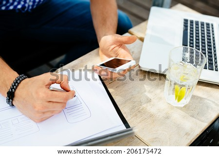 Close-up of a man sketching a blueprint of a new mobile application - stock photo