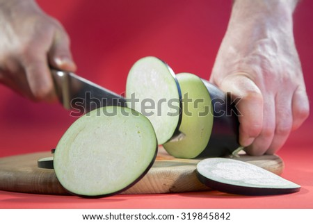 Close-up of a man slicing eggplant with a kitchen knife on cutting board.