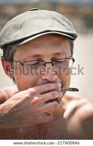 Close up of a man smoking hashish joint. - stock photo