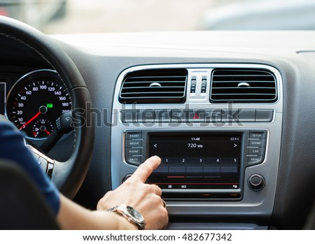 Close-up of a man touching dashboard with finger while sitting in car.