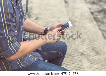 Close up of a man using and typing smart phone.