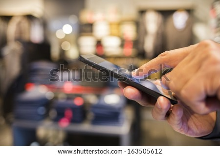 Close up of a man using Cell phone in clothing store - stock photo