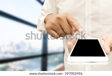 Close up of a man using mobile smart phone,blank black screen near big glass windows at office - stock photo