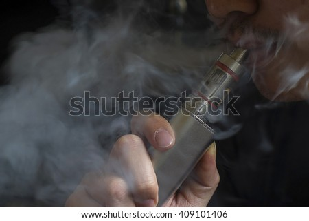 Close-up of a man vaping an electronic cigarette - stock photo