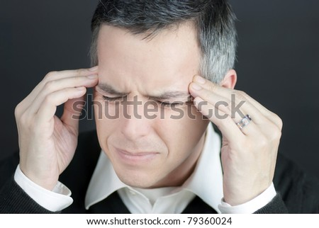 Close-up of a man with a migraine holding his temples. - stock photo