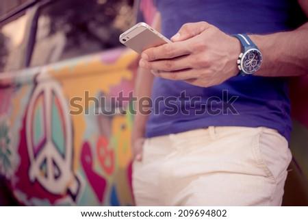 close-up of a man with athletic body holding a smartphone - stock photo