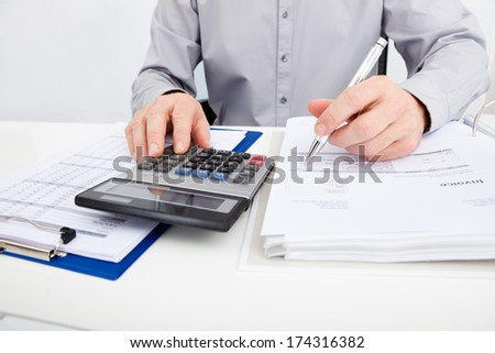 Close-up Of A Man With Financial Bills Using Calculator - stock photo