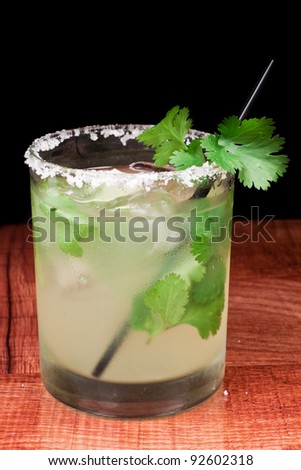 close up of a margarita garnished with a fresh lime and a salt rim around the glass - stock photo