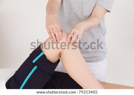 Close up of a masseuse massing the knee of an athletic woman - stock photo