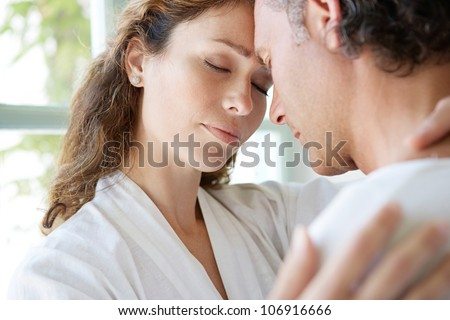 Close up of a  mature couple hugging at home, with their heads together. - stock photo