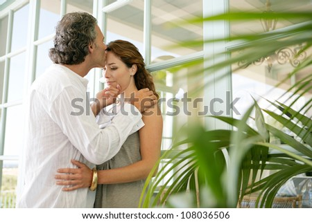 Close up of a  mature couple kissing at home, standing by large glass doors. - stock photo