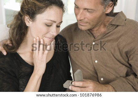 Close up of a mature man proposing marriage to a woman and offering her an engagement ring.