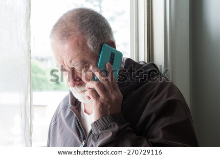 close-up of a mature man with a beard on his cell phone  - stock photo