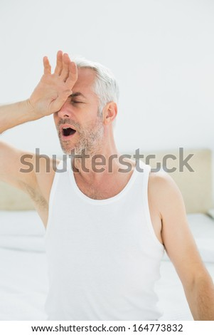 Close-up of a mature man yawning in bed at home