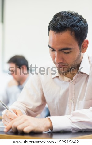 Close-up of a mature student taking notes in lecture in college