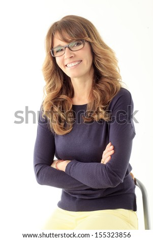 Close-up of a mature woman smiling and sitting against white background