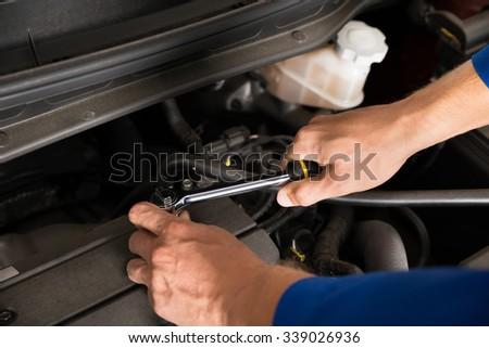 Close-up Of A Mechanic Repairing Car Using Screwdriver - stock photo