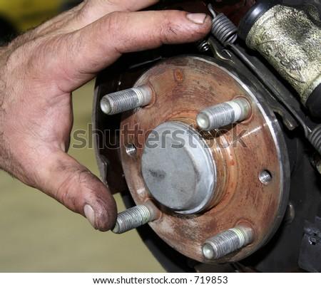 Close up of a mechanics hand on a wheel disc - stock photo