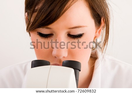 Close up of a medical student looking through microscope in laboratory - stock photo