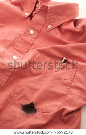 Close Up of a Men's Shirt with a Broken Pen that has Leaked Ink, Leaving a Stained Pocket that Needs to be Cleaned on White Background