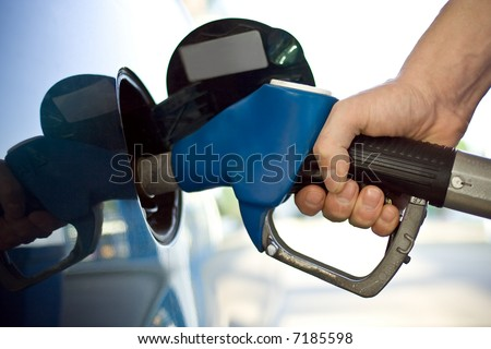 close-up of a mens hand refilling the car with a gas pump - stock photo