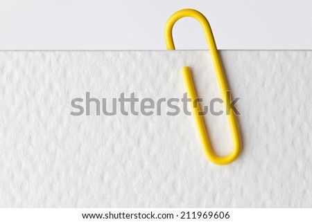 close up of a metal paper clip and paper on white background - stock photo