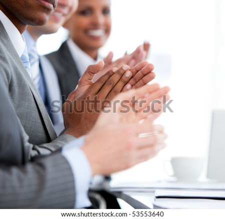 Close up of a  mixed business team applauding a presentation in the office - stock photo