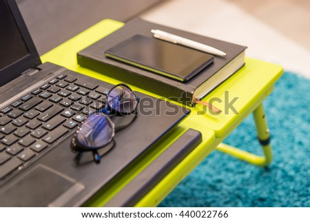Close up of a modern tabletop workstation with stylish eyeglasses lying on the keyboard of an open laptop computer with a diary and mobile phone alongside - stock photo