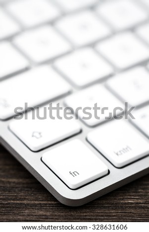 Close up of a modern white, gray computer keyboard. Focus on fn button. - stock photo