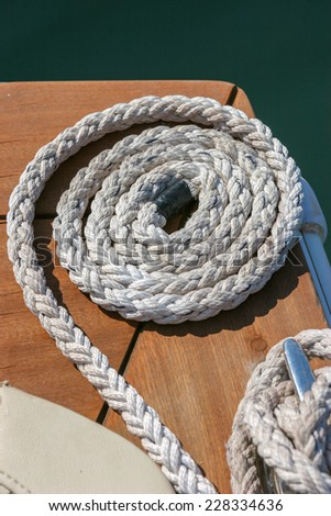 Close-up of a mooring rope tied around a cleat on a wooden pier - Nautical mooring rope - stock photo